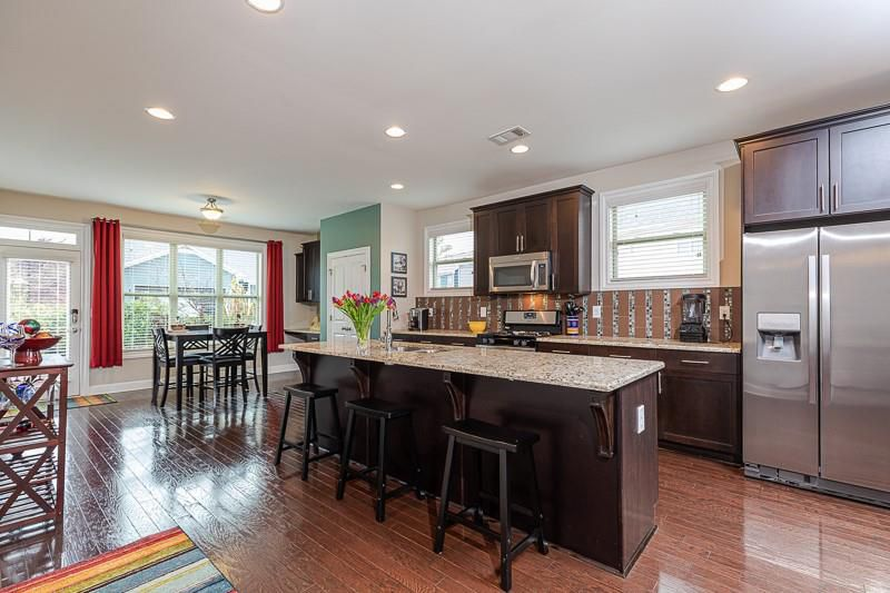 Large kitchen with island, barstools, dark cabinets and stainless refrigerator.
