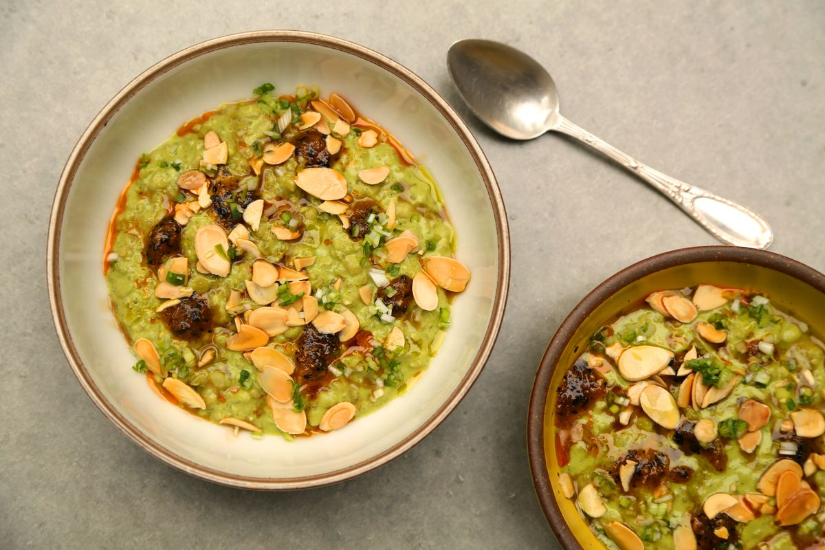 An overhead photo of a spoon and two bowls of green porridge topped with sunflower seeds