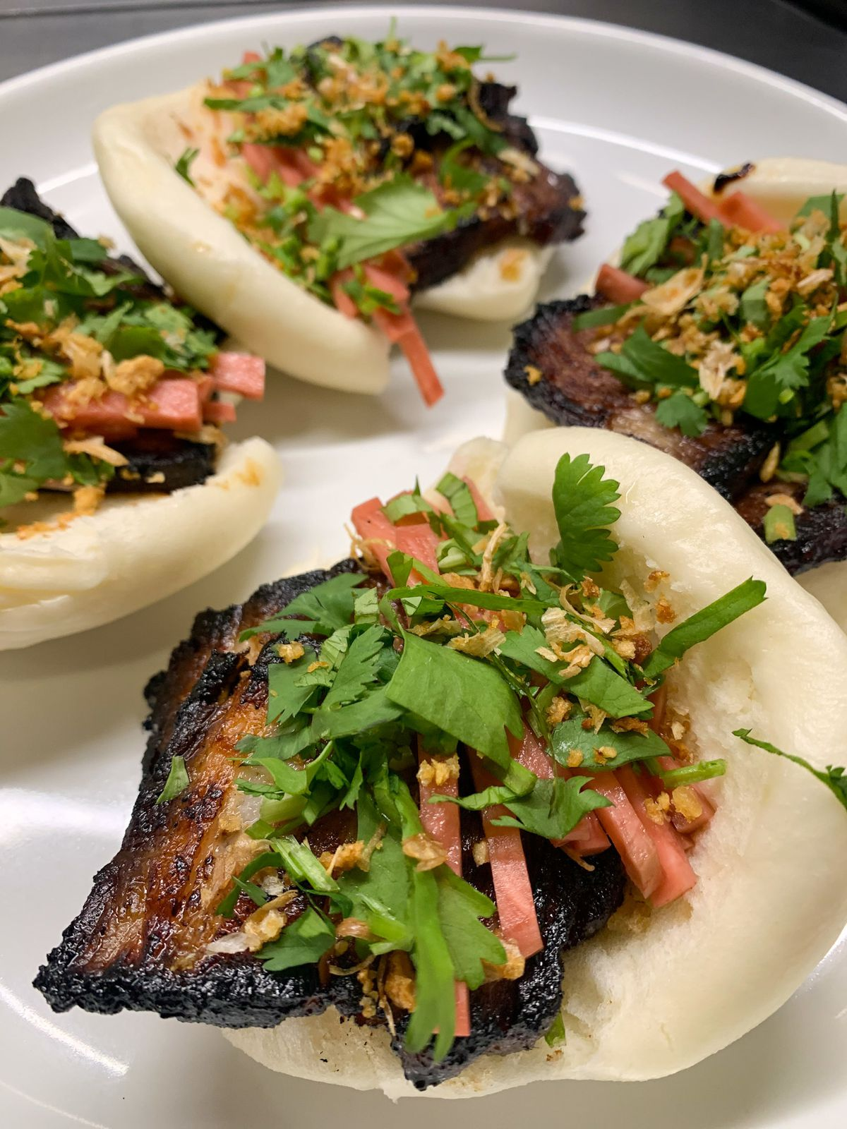 Four open-faced bao buns stuffed with pork and vegetables and placed on a white plate