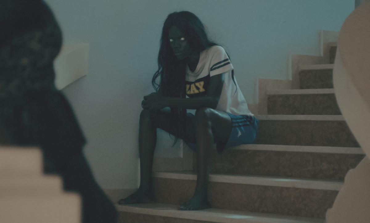A woman with milky eyes sits upon a staircase.