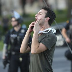 A protester decrying the police shooting of Bernardo Palacios-Carbajal yells at police in Salt Lake City on Thursday, July 9, 2020.