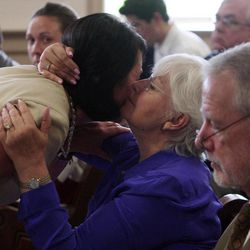 Michelle Ballotta Lowe, left, current co-chair of the pastoral council at St Patrick's Church in Chatham Boro gets a hug after her victim impact statement from Judith Ann Conk, a long time friend of Rev. Edward Hinds, Friday April 20, 2012 in Morris County Superior Court in Morristown, N.J. Jose Feliciano , a former church janitor was sentenced Friday to life in prison without parole for the 2009 stabbing death of a beloved New Jersey priest who had fired him.