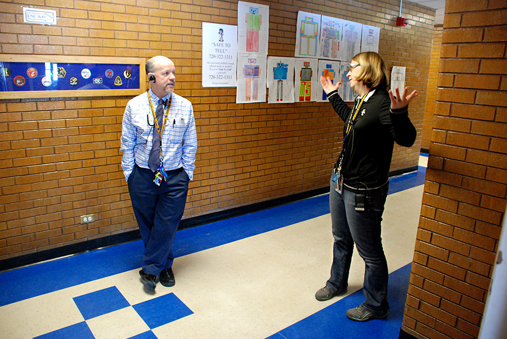 Assistant Principal Thomas Evans, left, and instructional coach Stephanie Rosch discuss logistics for the upcoming PARCC test in the hall.