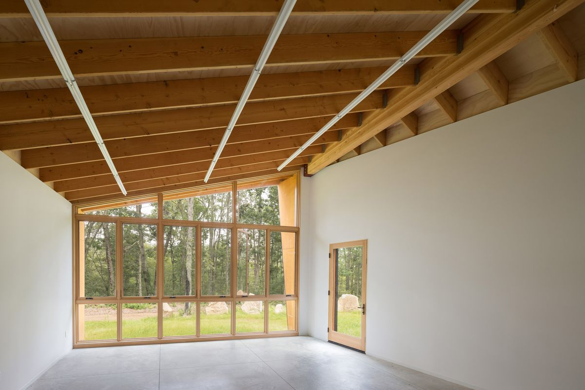 Interior of studio looking through large windows into forest