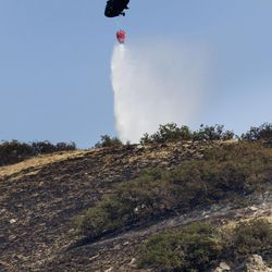 Water is poured on hot spots in Weber Canyon on Wednesday, Sept. 6, 2017. At least six structures, including multiple homes, have been destroyed after a brush fire that erupted in the canyon Tuesday morning.