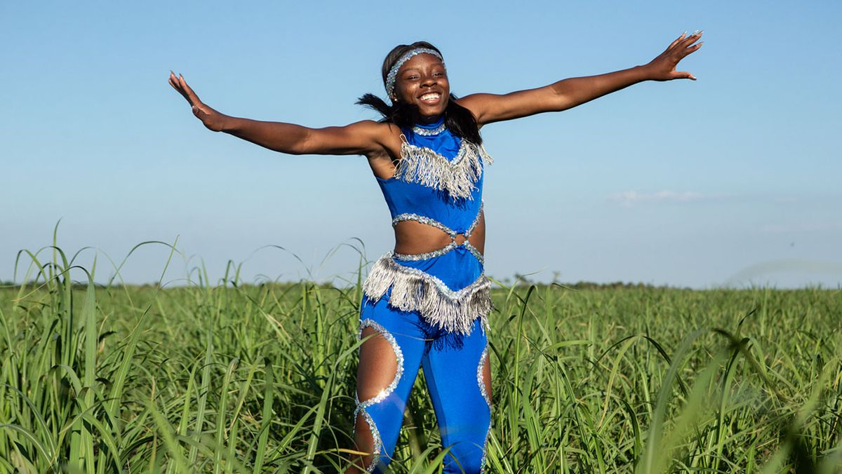 A teenager in a blue cheering outfit in a field in Pahokee.