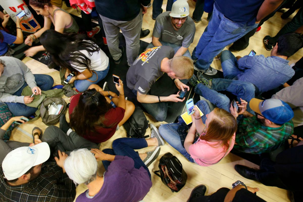 A crowd of people sitting on the floor, all looking at their cellphones