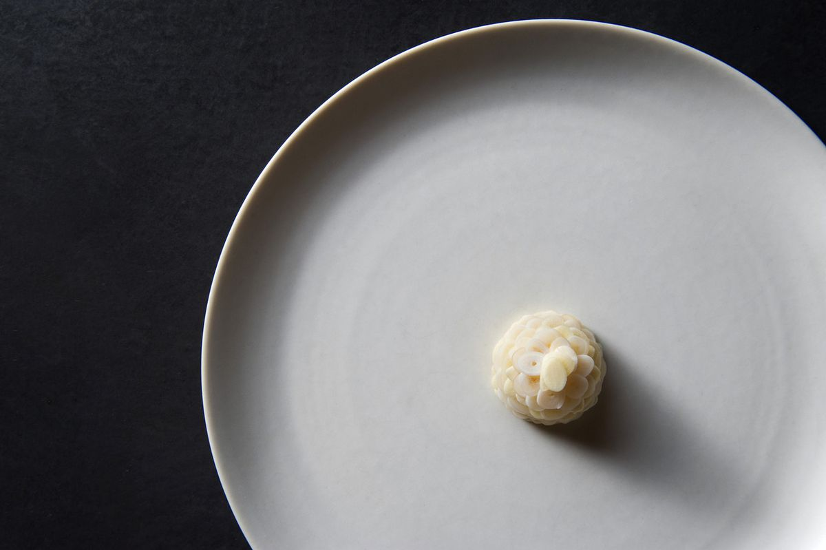 A white plate holds razor clam topps with thin slices of pickled garlic.