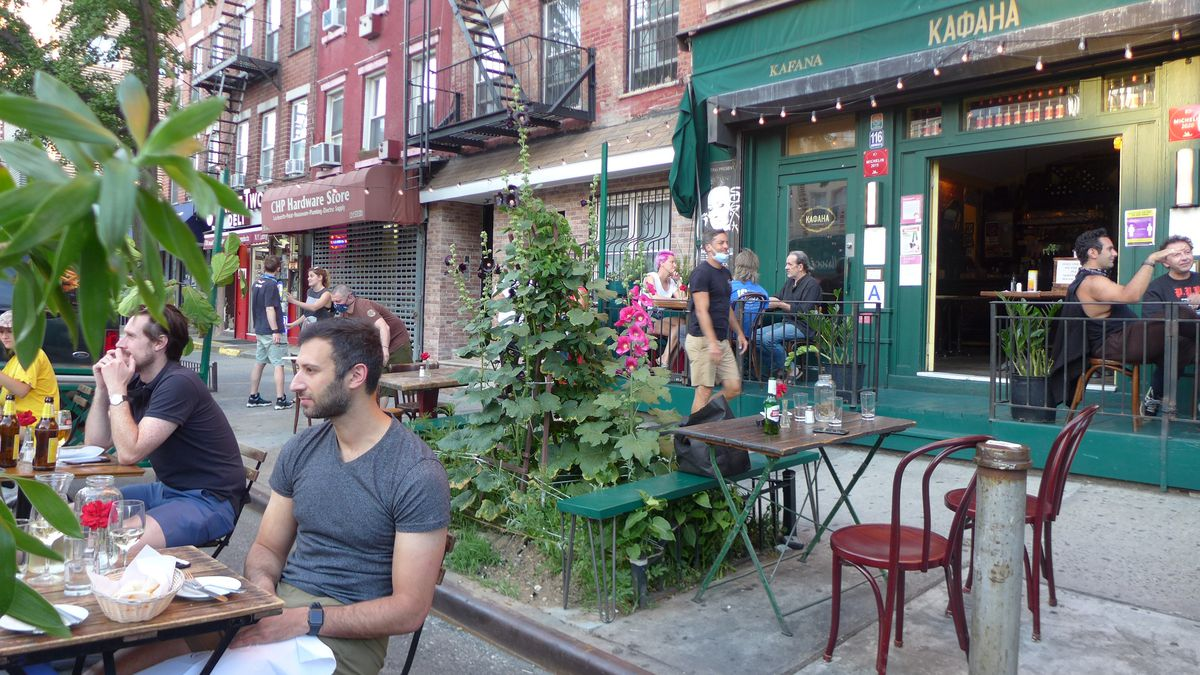 A sidewalk cafe showing a few people relaxing at tables in parking spots in the street.