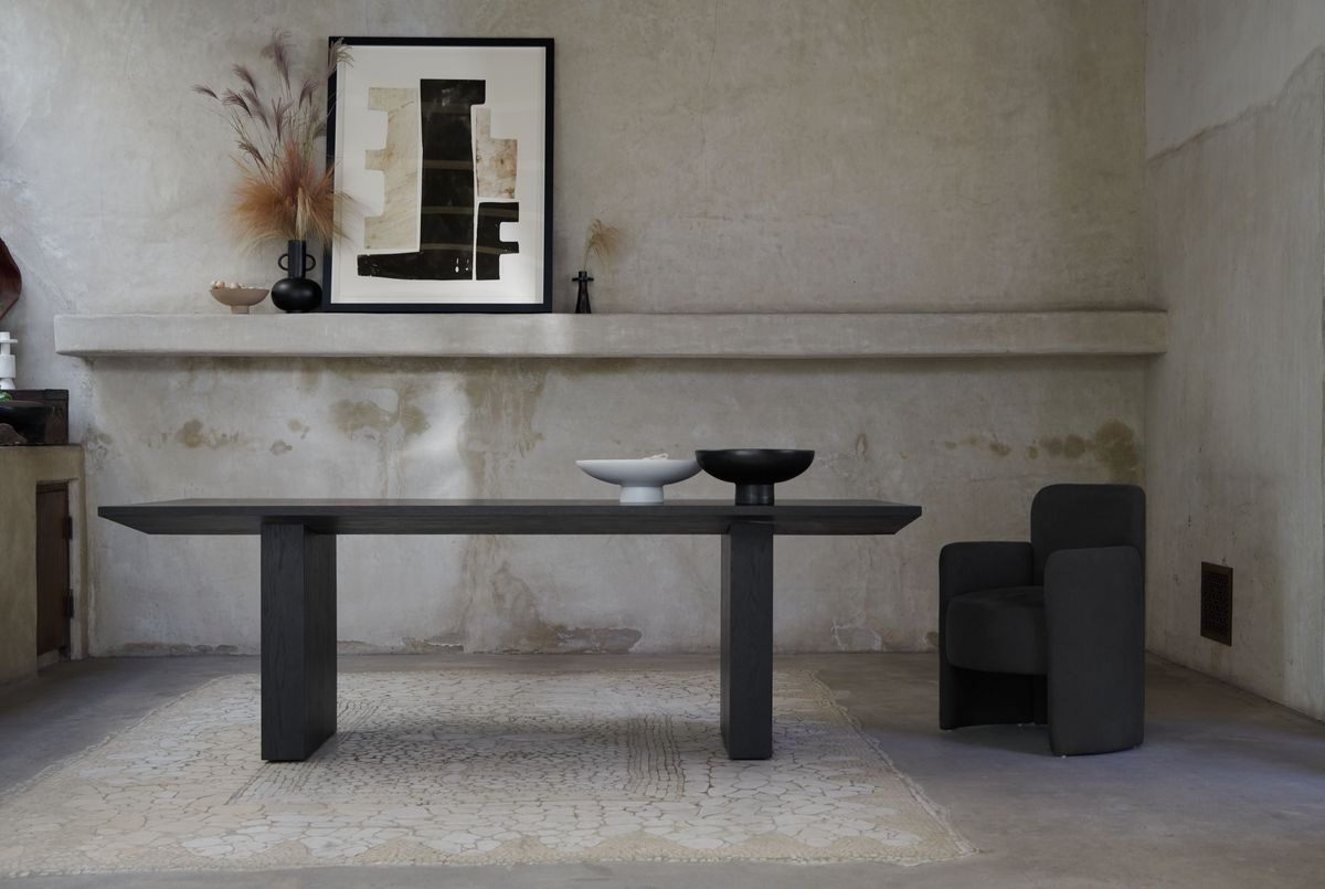 Dining room table in dark wood in a concrete room.
