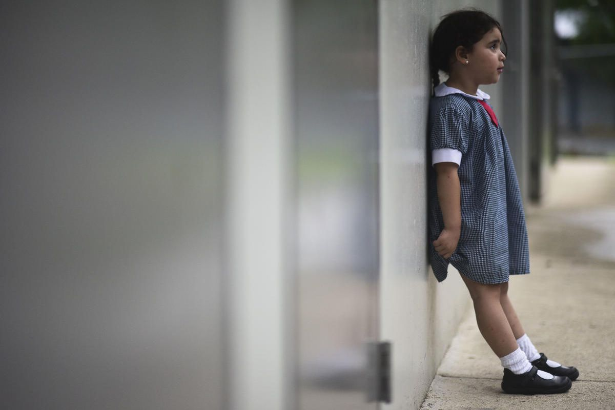 """In this Friday, Oct. 13, 2017 photo, a girl waits for her mother in the hallway of Ramon Marin Sola Elementary School, which opened its doors as a daytime community center after the passing of Hurricane Maria in Guaynabo, Puerto Rico. """"We're trying teach"""