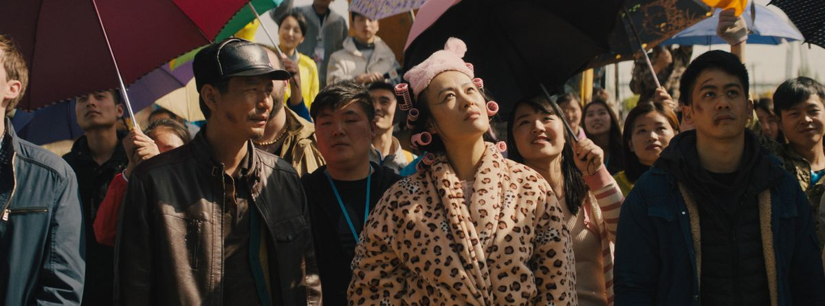 A woman in a leopard print bathrobe and hair curlers stares dismissively at something above her.