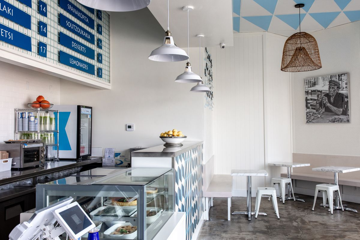 A blue and white fast casual restaurant with deli counter and mounted menu.