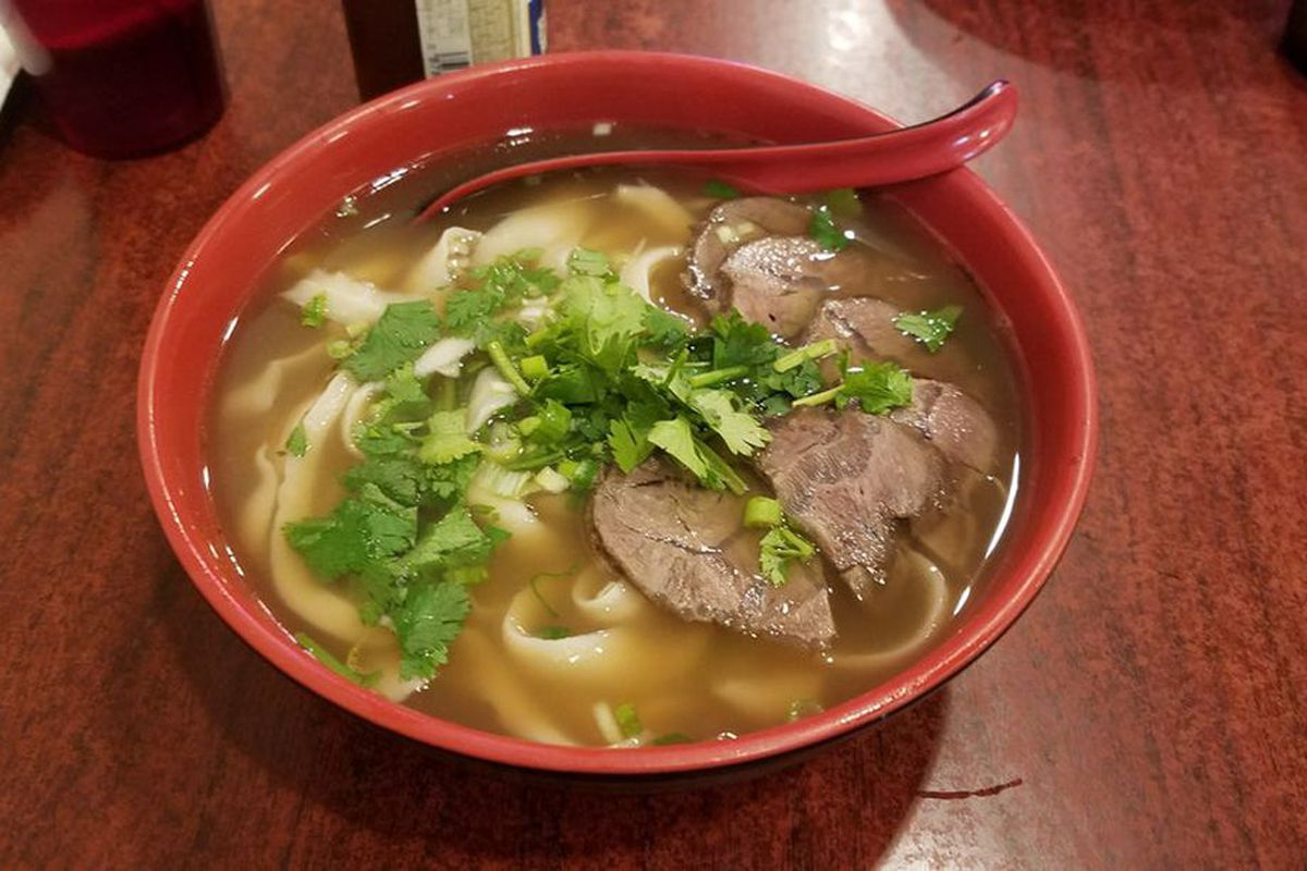 Hand-pulled noodles in broth topped with beef and cilantro