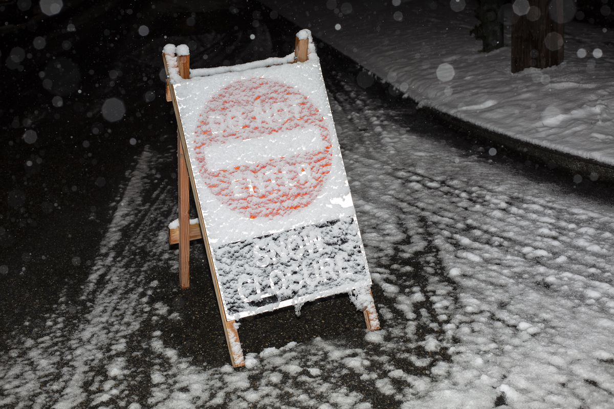 """A """"Do Not Enter/Snow Closure"""" sign sits on a snowy block at night covered in a layer of snowflakes, with the letters barely legible"""