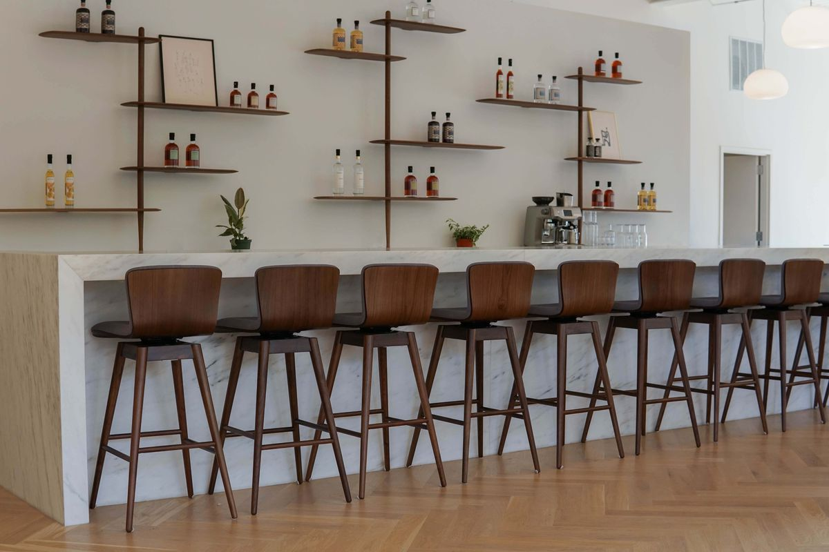 A long white marble bar with eight tall, dark wood chairs