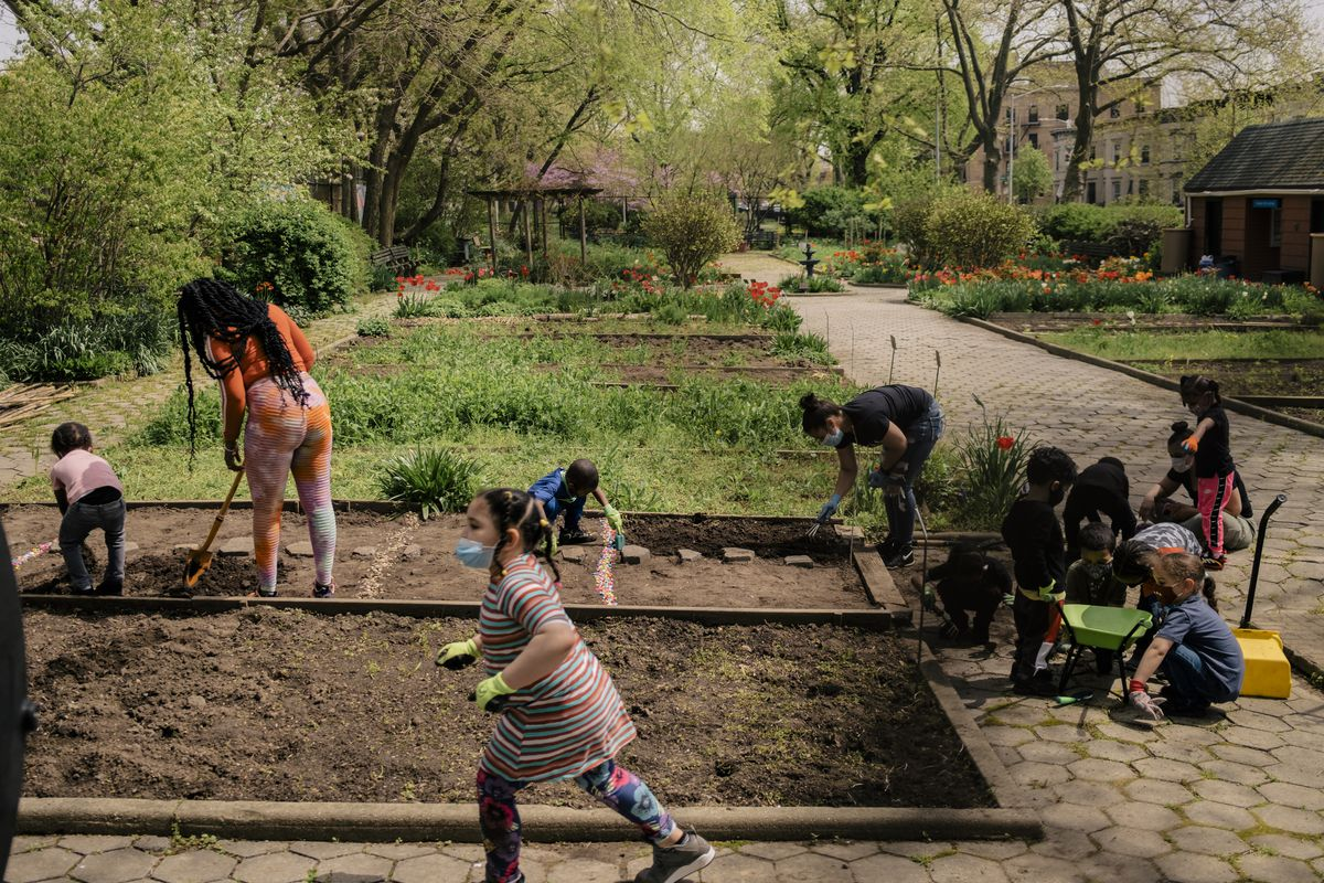 A group of kids and two women work in a community garden. A girl wearing a striped dress runs with dirt in her hands in the foreground as they work on two bare plots.