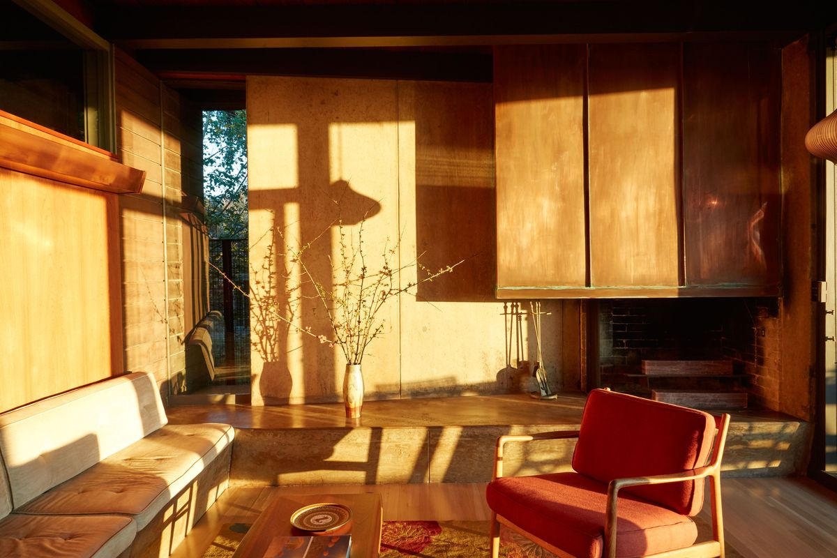 A living area. There is a bench, a wooden coffee table, a red arm chair. The walls are all wood paneled. There is a copper fireplace hood over a fireplace.