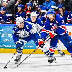 Syracuse Crunch Taylor Raddysh (18) battles for the puck with Rochester Americans Zach Redmond (22) in American Hockey League (AHL) action at the War Memorial Arena in Syracuse, New York on Saturday, December 8, 2018. Rochester won 4-3.