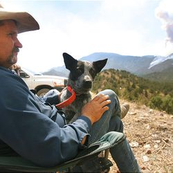 Sixth-generation New Harmony resident Brent Prince sits with his dog Bandit on Little Mountain watching the Mill Flat fire on Sunday. Eleven structures burned over the weekend, but no injuries have been reported.