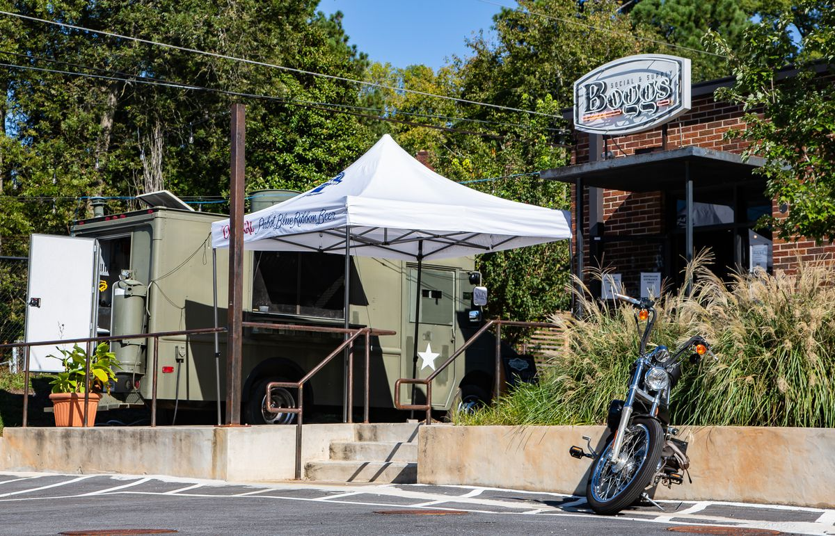 The army green Korean food truck parked at the patio at Bogg's Social and Supply in West End Atlanta. A white tent is set up around the to-go window of the truck. A motorcycle is parked outside the restaurant and bar