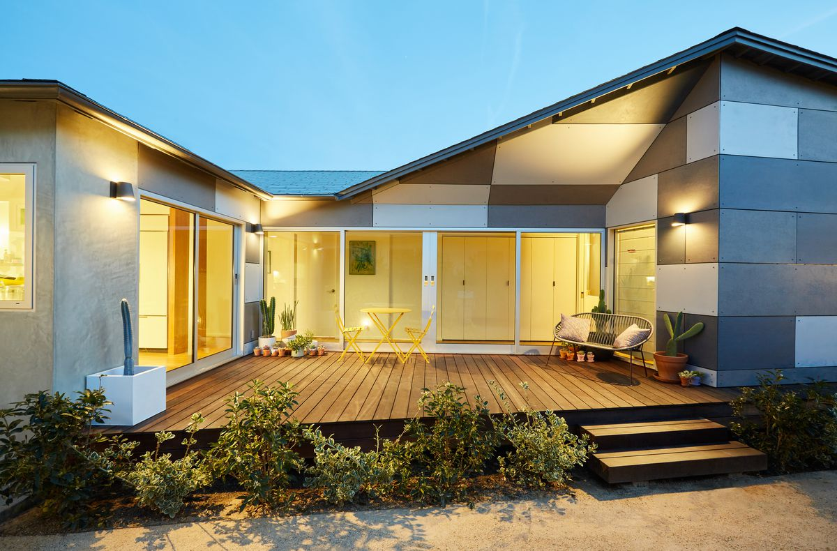 The exterior of a house with multicolor concrete panels. Lights from the interior illuminate the facade. There is a wooden deck and floor to ceiling windows.