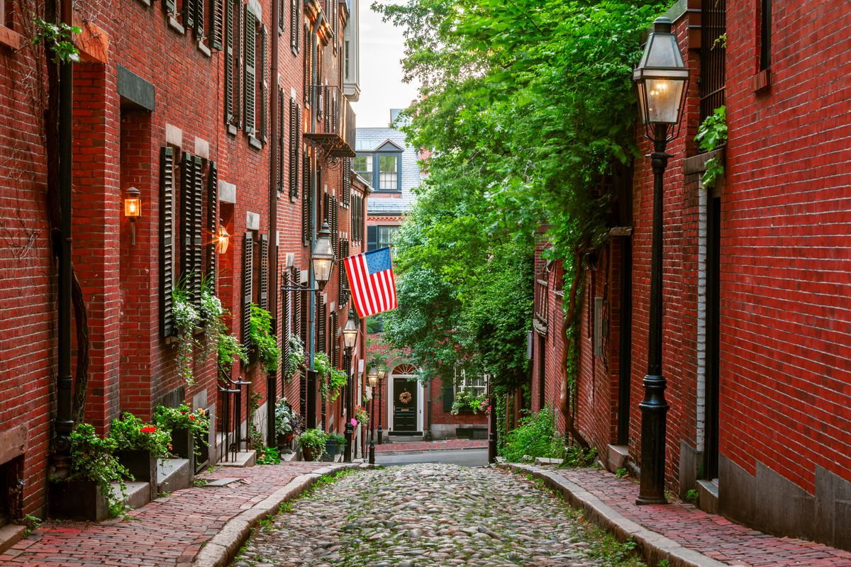 Acorn Street in Boston. The street is cobblestone and the buildings lining the street are red brick with black shutters.