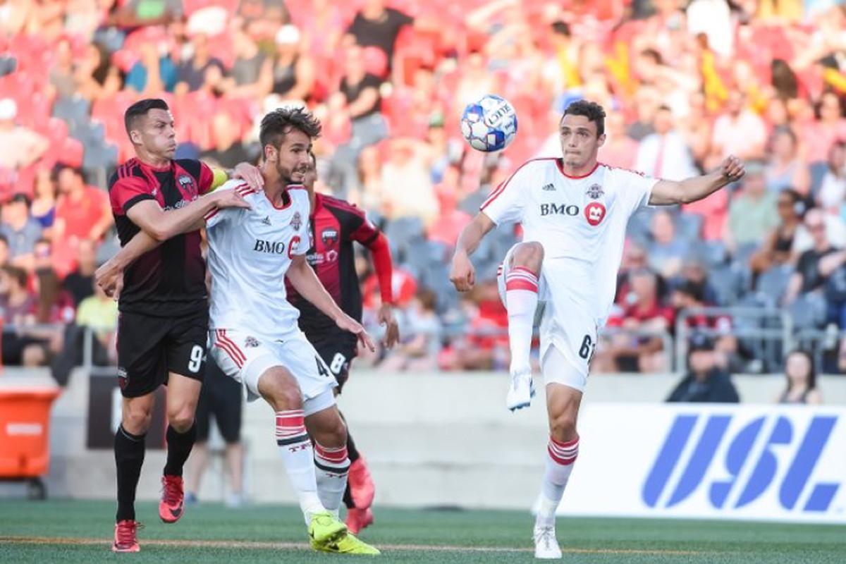 USL Photo - Toronto FC II defenders Robert Boskovic and Rocco Romeo seek to hold off an Ottawa Fury FC attack