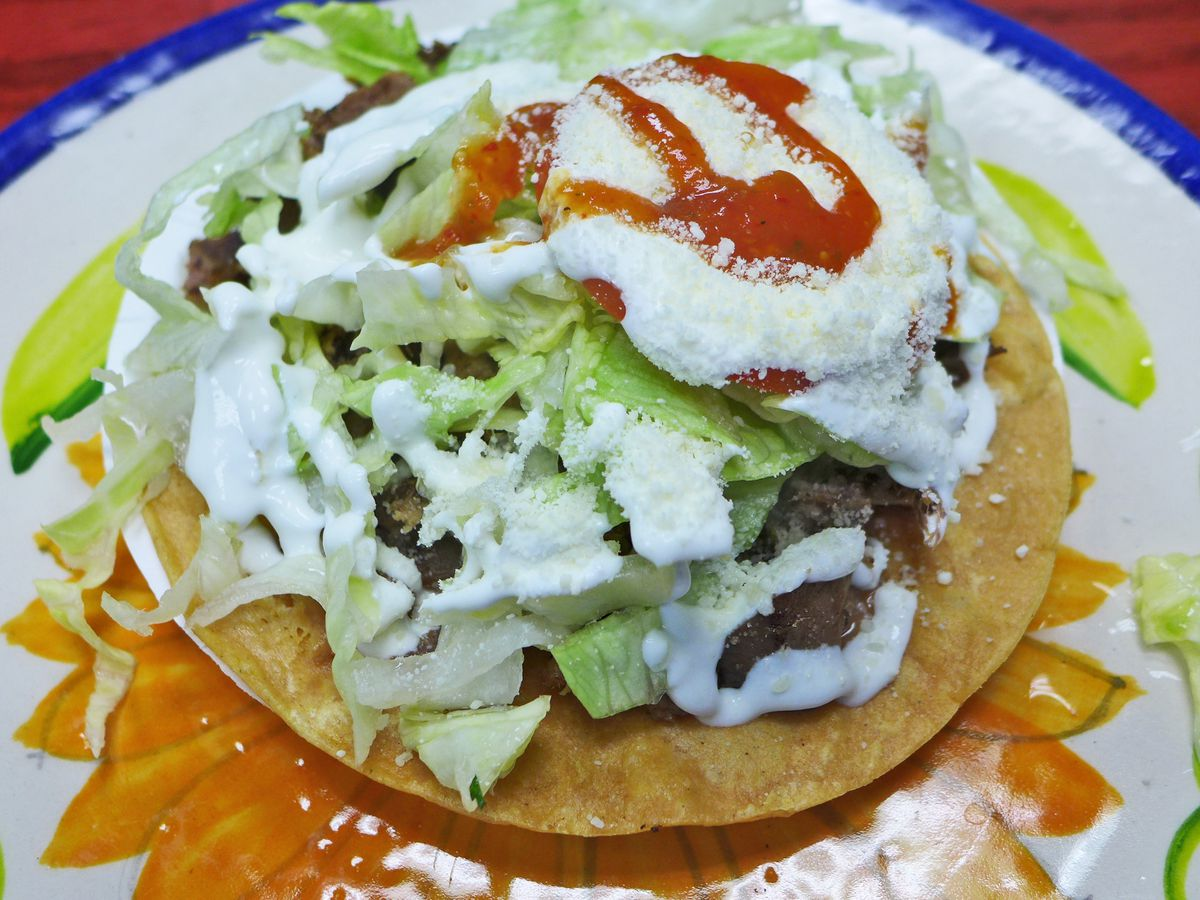 A tostada so covered with cheese, crema, and foliage that you almost can't see the dark tongue underneath.