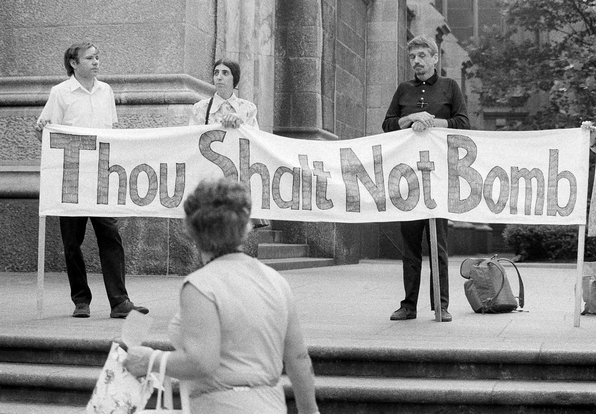 This July 25, 1973, photo shows the Rev. Daniel Berrigan, right, with others participating in a fast and vigil to protest U.S. bombing in Cambodia, on the steps of St. Patrick's Cathedral in New York City. AP file photo