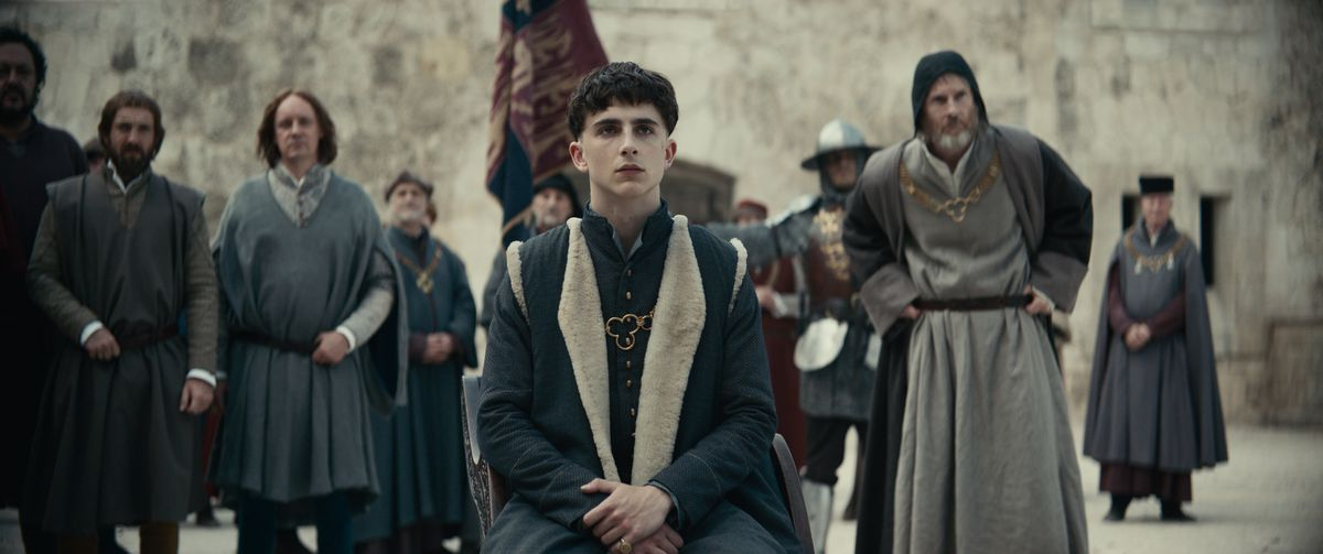 Henry (Chalamet) sits in front of a group of his subjects.