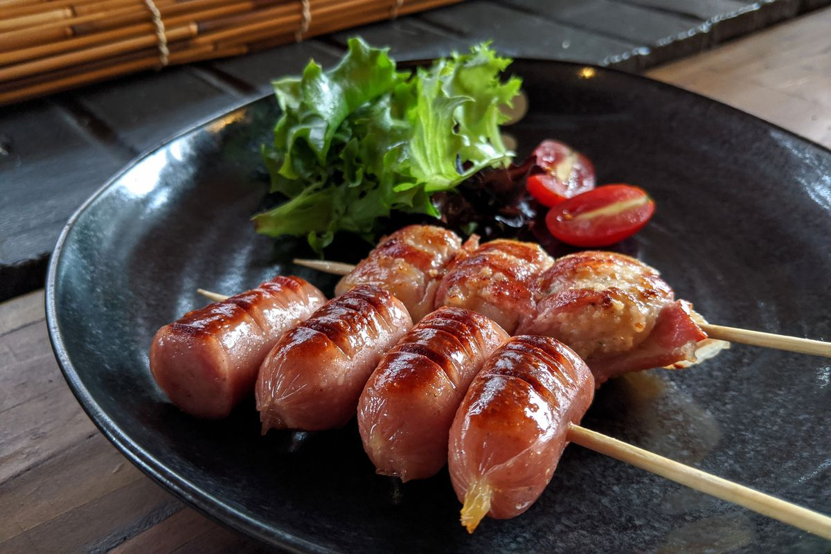 Two wooden skewers of meat on a blue plate — one with pieces of Japanese sausage and one with bacon-wrapped scallops - with a side of greens and sliced cherry tomatoes.