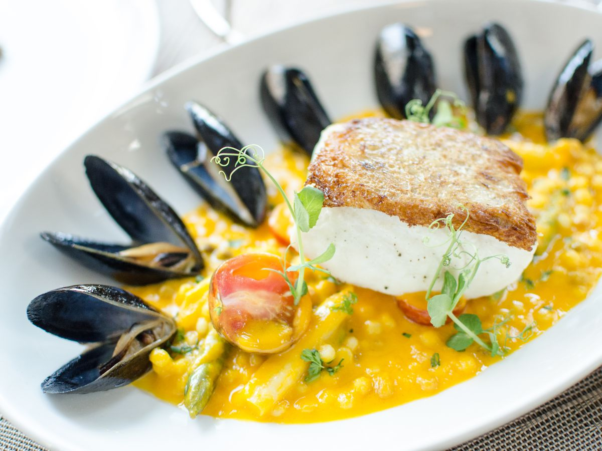 A thick piece of halibut topped with a crispy breading sits in a yellow pool of sauce with asparagus, tomatoes, small round pasta bits, and mussels.