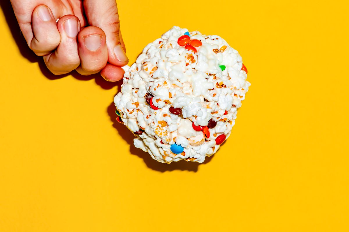 A hand holding a popcorn M&M ball on a stick against a yellow background