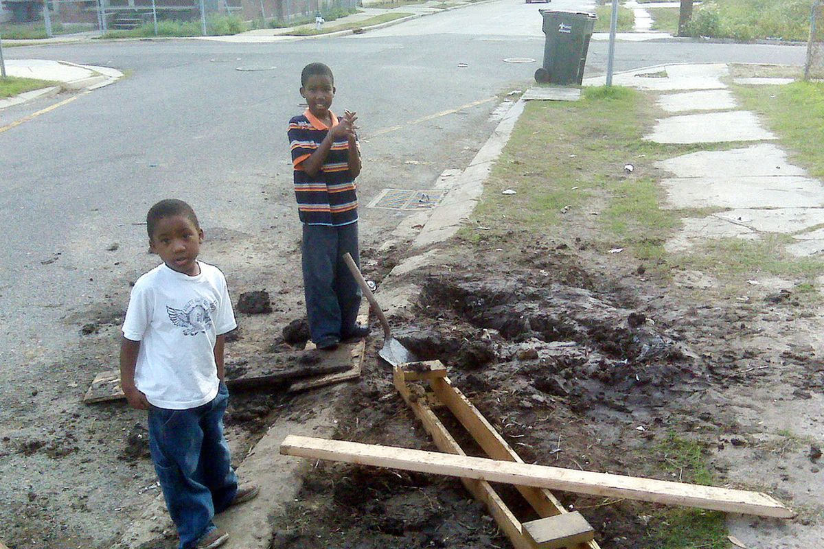 Two kids playing in dirt in Mid-City New Orleans.