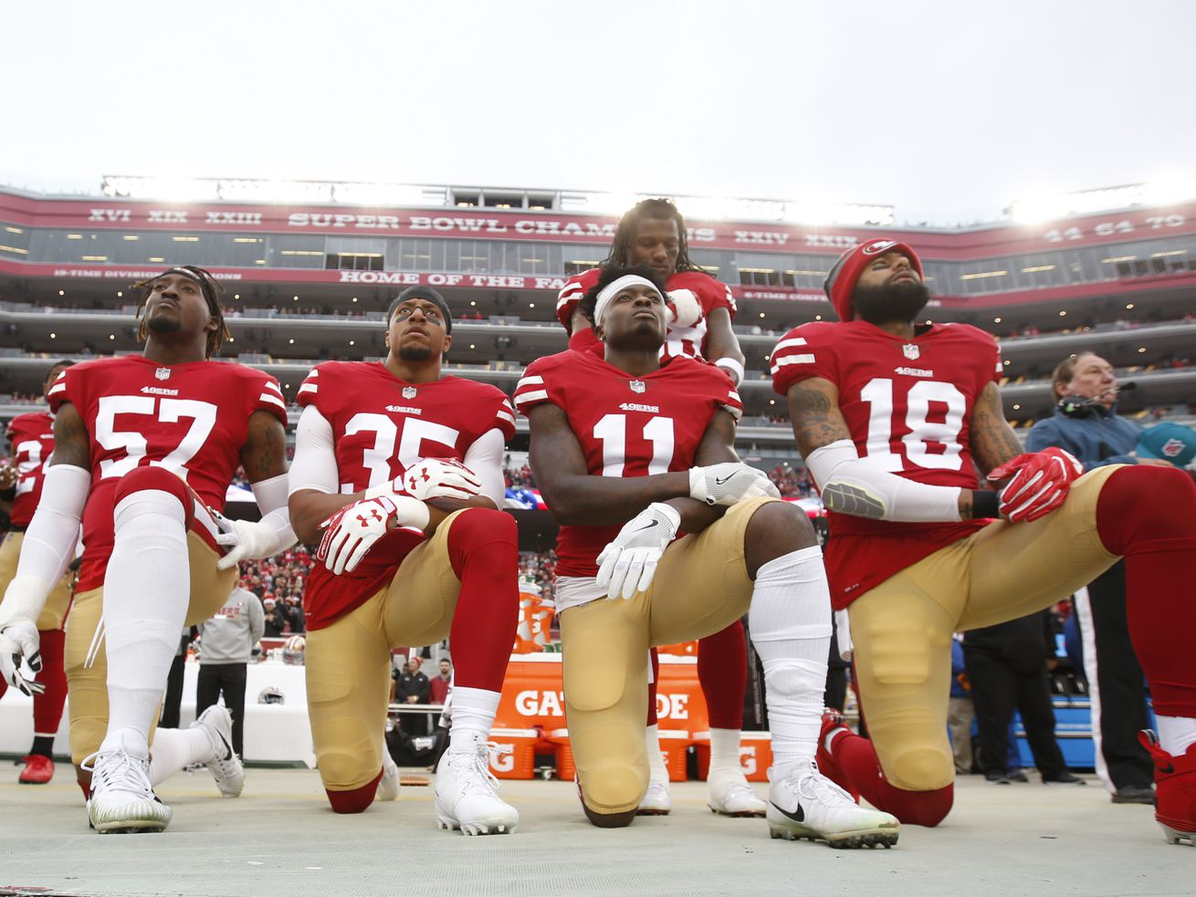 Members of the San Francisco 49ers kneel in protest.
