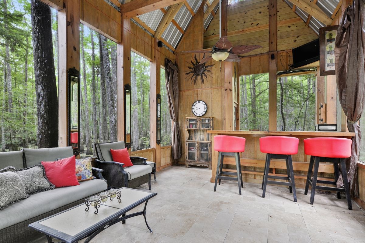 A woodsy cabin with swamp views has high vaulted ceilings and a tin roof.