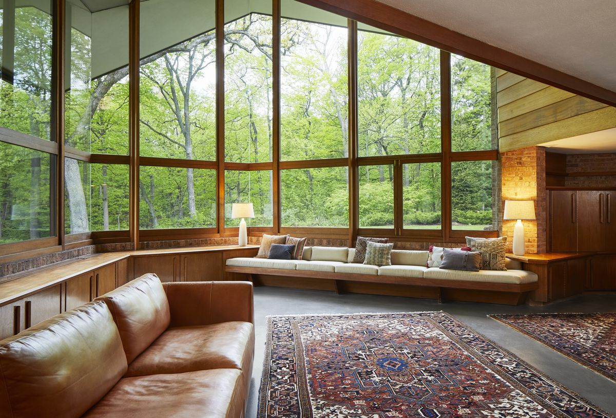 Large windows look out to a lovely, tree-filled forest.
