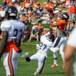 Between the people in the foreground, you can see Broncos WR Jordan Leslie (19) go up for a pass over Bears DB Sherrick McManis (27) during training camp.