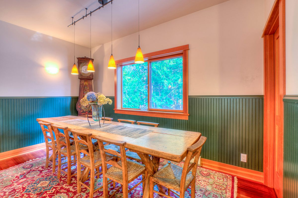 A dining room with green wainscoting on the walls and four overhead lights over a long table. A grandfather clock and a window to outside are in the background. There is a door to the right.