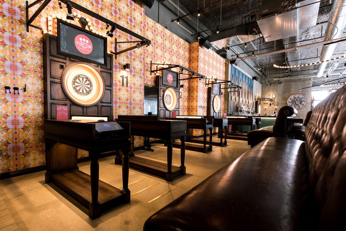 A wall of darts games set up with a large leather booth, at the Flight Club bar in Chicago.