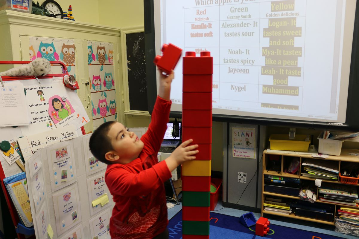 A pre-K student at P.S. 277 in the Bronx builds a block tower.
