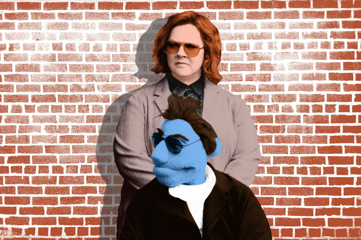 Melissa McCarthy and a blue muppet wearing sunglasses standing in front of a brick wall
