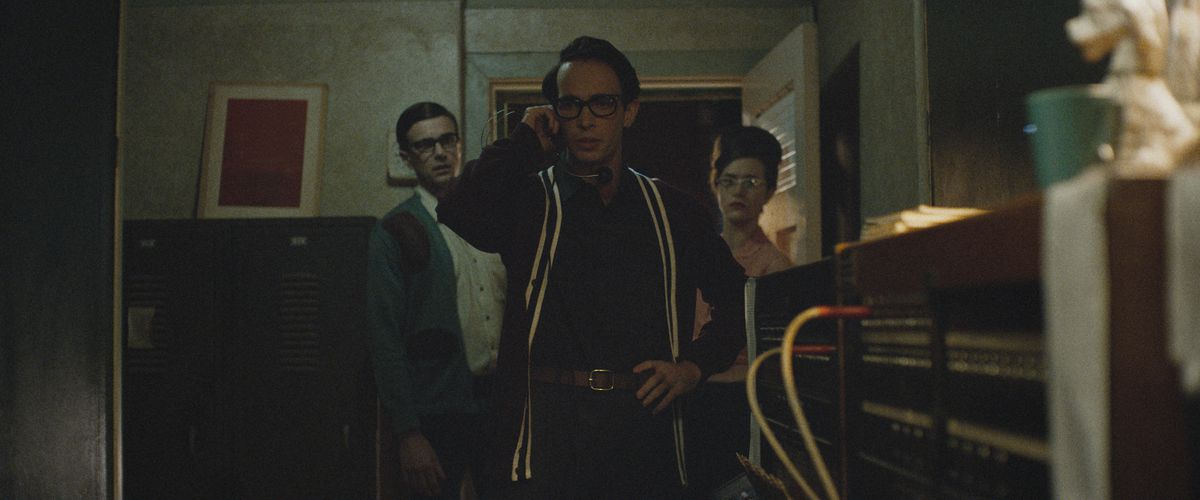 Jake Horowitz stands in the open door of a switchboard room, talking on a headset in The Vast of Night