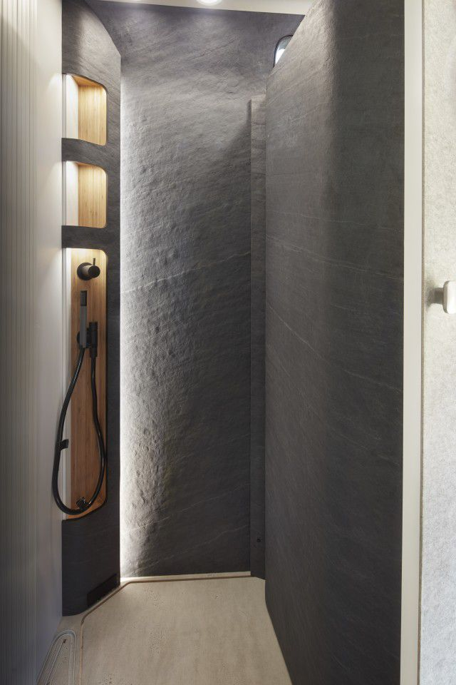 Slate walls in a modern shower, with a wooden strip that boasts gray shower fixtures.