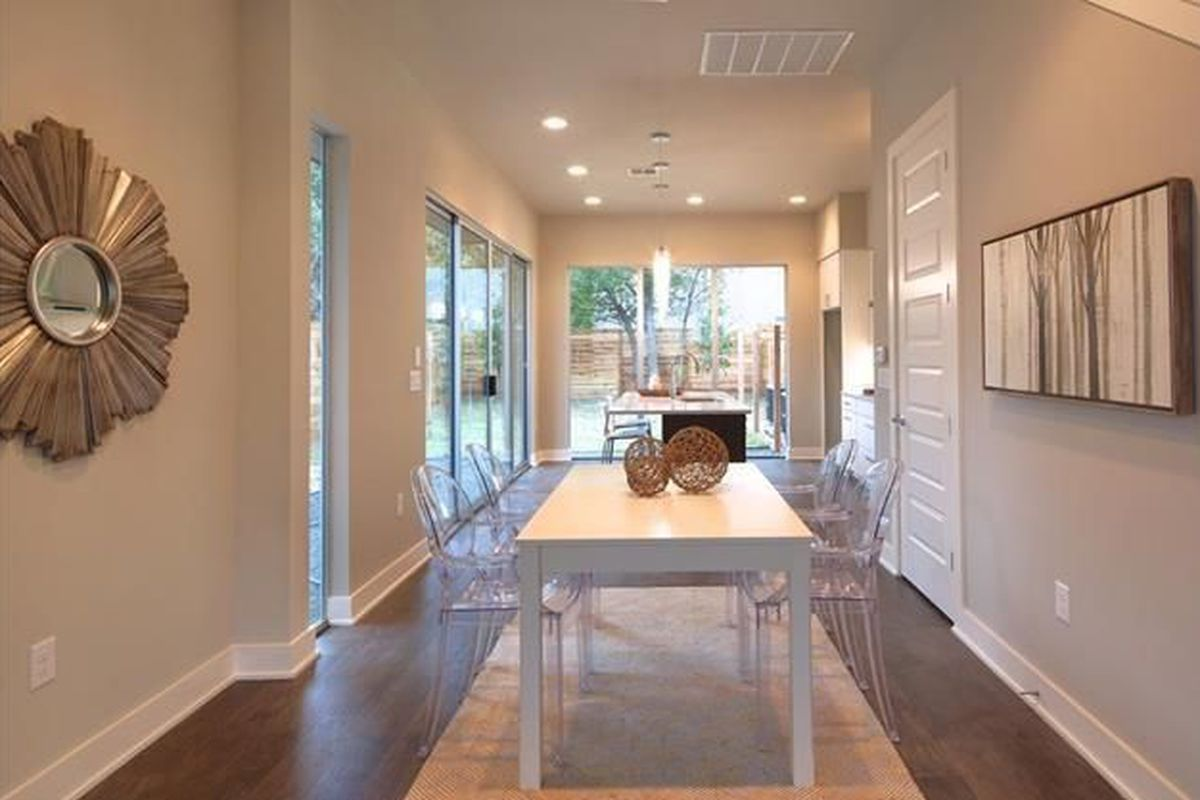 Long, white room with big windows and sliding glass doors on two sides at end, panel door, white table, concrete floor