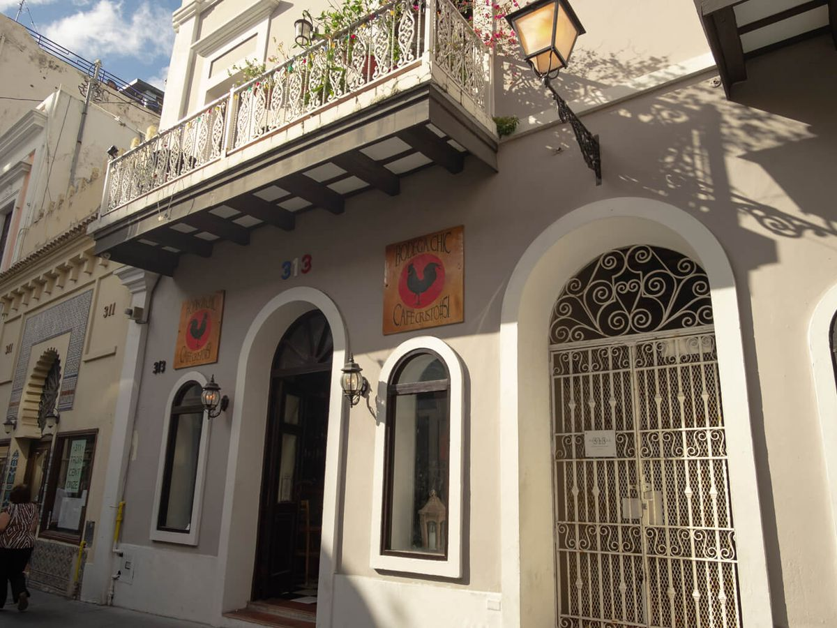 A building exterior with classic San Juan Spanish colonial architecture and signage for Bodega Chic restaurant