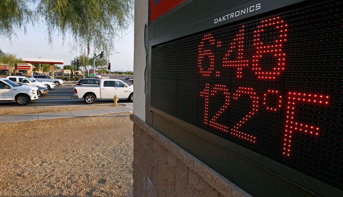 An electronic sign displays extreme temperature as car line up in a street in the background.