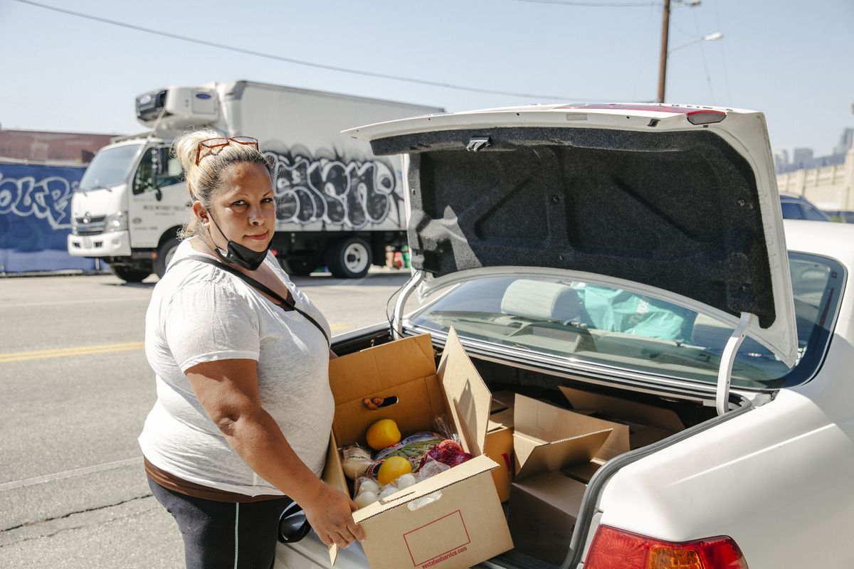 Woman carries a box containing food into the trunk of a car.