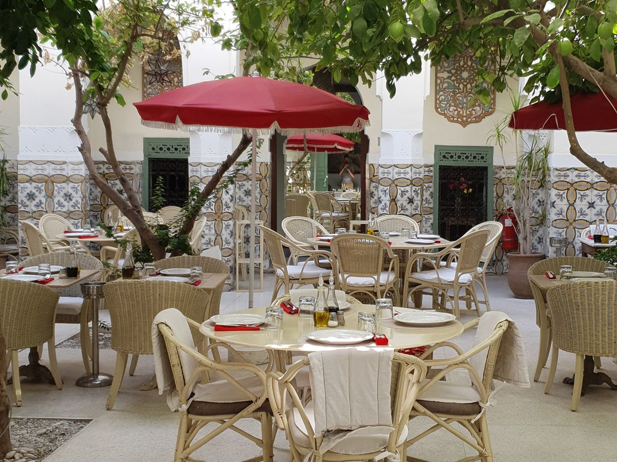 An empty interior courtyard with large trees providing shade for set patio tables